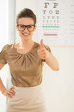 Woman wearing eyeglasses showing thumbs up near Snellen chart Stock Image