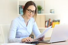Woman calculating with a calculator at home stock photo
