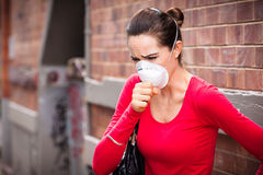Woman wearing facemask coughing Stock Photo