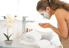 Woman wearing facial cosmetic mask washing face Royalty Free Stock Image
