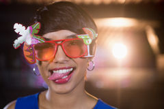 Woman wearing fancy sunglasses making funny faces in bar Royalty Free Stock Image