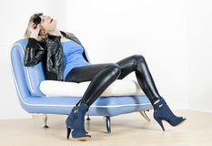 Woman wearing fashionable shoes. Sitting on sofa Stock Photography