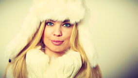 Woman wearing fashionable wintertime clothes. Winter fashion. Young blonde woman wearing fashionable wintertime clothes white fur scarf cap, woolen gloves Stock Image