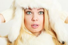 Woman wearing fashionable wintertime clothes. Winter fashion. Young blonde woman wearing fashionable wintertime clothes white fur scarf cap, woolen gloves Royalty Free Stock Images