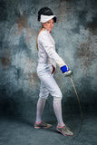 The woman wearing fencing suit with sword against gray Stock Photography