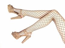 Woman wearing fishnet stockings and golden heels shoes. Legs of a woman in shiny golden platform high heels shoes and fishnet stockings Royalty Free Stock Photo