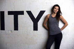 Woman Wearing Fitness Clothing Standing Against Wall Of Gym Royalty Free Stock Images