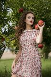 Woman wearing floral long dress against pomegranate trees. Young woman wearing floral long dress standing against pomegranate trees, facing the camera as she Stock Images