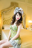 Woman wearing floral wreath on had. Beautiful young woman wearing floral wreath on had sitting on bed Stock Photo