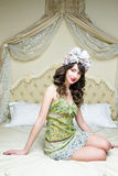 Woman wearing floral wreath on had. Beautiful young woman wearing floral wreath on had sitting on bed Royalty Free Stock Images