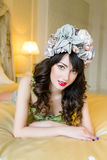 Woman wearing floral wreath on had. Beautiful young woman wearing floral wreath on had sitting on bed Stock Images
