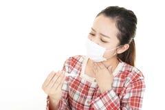 Woman got a cold. Woman wearing a flu mask royalty free stock image