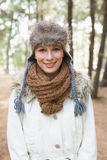 Woman wearing fur hat with woolen scarf and jacket in woods Royalty Free Stock Images