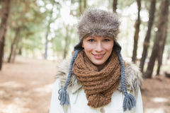 Woman wearing fur hat with woolen scarf and jacket in woods Stock Photos