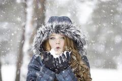 Woman wearing fur hood in a snow storm