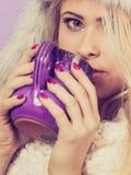 Woman wearing furry hat holding mug Stock Image