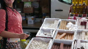 A woman wearing glasses buys oriental sweets in the Turkish market in the summer stock video footage