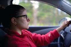 Woman wearing glasses drives car and is concentrated looks at road Stock Photos