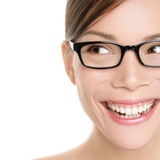 Woman wearing glasses looking happy to side. Eyewear woman with big smile wearing eyeglasses. Close up portrait of female spectacles model isolated on white Stock Photography