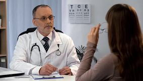 Woman wearing glasses, ophthalmologist watching and helping to choose spectacles. Stock photo stock photo