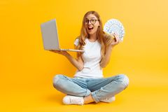 Woman wearing glasses sitting on the floor using a portable laptop and holding money in her hand, on a yellow background stock image