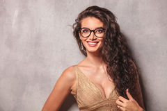 Woman wearing glasses and smiling while arranging her hair Royalty Free Stock Photo