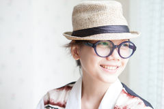 Woman wearing a glasses and straw hat smilling Stock Photography