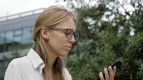 Woman wearing glasses using a smart phone voice recognition function outdoors.