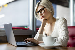 Woman Wearing Glasses While Working On Laptop In Cafe Stock Photography