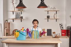 Woman wearing gloves, holding with a sponge in his hands, bowl full of bottles with disinfectant on table. Emotional Housekeeper. Beautiful woman cleaning stock images