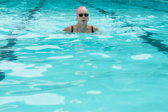 Woman wearing goggles while swimming in pool. Mature woman wearing goggles while swimming in pool Stock Photos