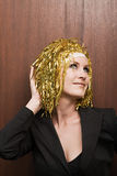 Woman wearing gold color wig Stock Images