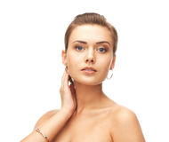 Woman wearing gold earrings and bracelet Stock Photos