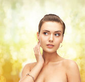 Woman wearing gold earrings and bracelet. Beauty and jewelry concept - beautiful woman wearing gold earrings and bracelet Stock Images