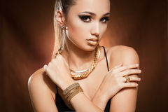 Woman wearing gold jewelry. Stock Image
