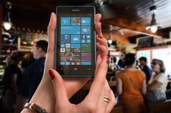 Woman Wearing Gold Ring Holding Blue Nokia Windows Smartphone Stock Image