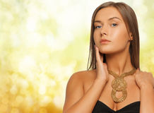 Woman wearing golden necklace over yellow lights Royalty Free Stock Images