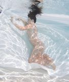 Woman wearing a gown holding her breathe underwater. Stock Photo
