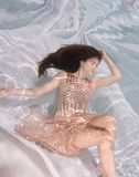Woman wearing a gown holding her breathe underwater. Stock Photos