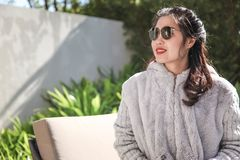 Woman Wearing Gray Fur Coat and Sunglasses Sitting Near Green Leaf Plants Stock Photography