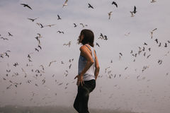 Woman Wearing Gray Racerback Under Flying Gray and Black Birds Stock Images