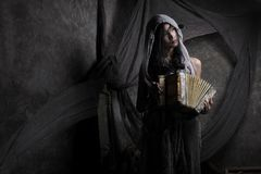 Woman Wearing Gray Scarf Holding Accordion stock images