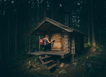 Woman Wearing Gray Shirt in Front of Brown Wooden Cabin at the Forest Stock Photo
