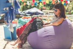 Woman Wearing Gray Tank Top Sitting on Purple Bean Bag Stock Photo