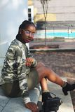 Woman Wearing Green, Black, and White Camouflage Sweatshirt Sitting on Concrete Ground Posing for Photo