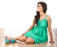 Woman wearing green dress sitting on the floor Royalty Free Stock Images