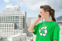 Woman wearing green recycling tshirt talking on the phone Stock Images