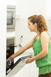 Woman wearing green top in modern kitchen holding Royalty Free Stock Images