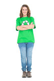 Woman wearing green tshirt with recycling symbol crossing arms. On white background Royalty Free Stock Photos