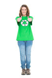 Woman wearing green tshirt with recycling symbol giving thumbs up. On white background Stock Photos